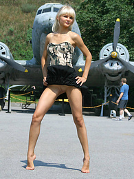 Gorgeous cheeky angel is wearing military clothes and poses near grenade launcher, tank and different army airplanes. pictures at kilomatures.com