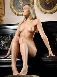 Fascinating nude coquette is posing near the black piano in one of the rooms of a famous grant museum. pictures