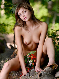 Fabulous nude kitten is sitting in the forest in bright read garland and poses energetically in front of the camera. pictures at sgirls.net