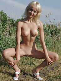 This startling thrilling with fully nude zones of the captivating body wanders across the deserted green field. pics