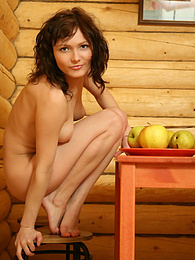 Dainty nude angel looks extremely sexy when dancing on the table with apples in the little wooden house of hers. pictures at lingerie-mania.com
