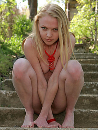 Unbelievable blue-eyed blonde honey is observed to pose on the stone stairs fully nude at daytime in the green bushes. pictures