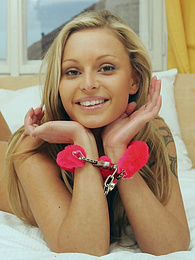 Handcuffed blonde gets naked on her bed pictures