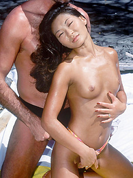 Young asian girl takes on two cocks at a tropical beach pictures at freekilomovies.com