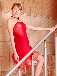 Lovely teen girl in a see-through red dress poses on the stairs, revealing slowly her nudeness pictures at find-best-hardcore.com