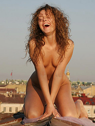 Creative pics of a gorgeous curly girl posing absolutely nude on the roof of an old building pictures at kilomatures.com
