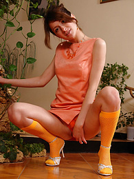 Cute playful brunette in raunchy orange knee-highs looses her tiny panties and poses nude pictures at freekilomovies.com