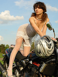 Fresh brunette girl takes off her white dress and stockings, posing on a sport bike pictures at kilomatures.com