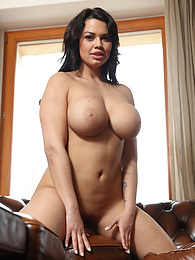 Brunette babe Chloe Lamoure exposes big tits on the leather sofa pictures at find-best-ass.com
