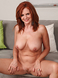 Mature redhead Andi James slowly strips naked on the sofa pictures